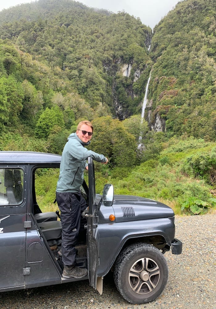 Chile, Puyuhuapi, Charlie hanging out of car infront of waterfall