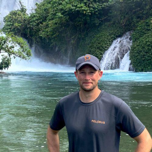 Jimmy in front of a waterfall in the Solomon Islands
